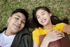 Jugendliche mit den Büchern, die auf grünem Gras liegen lizenzfreies stockbild