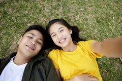 Jugendliche mit den Büchern, die auf grünem Gras liegen stockfoto