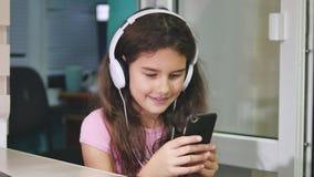 Jugendliche mit den Kopfhörern, die mit Spielen einen Smartphone sitzen Schulmädchenmädchen, das zuhause Online-Spiel auf Smartph stock video footage