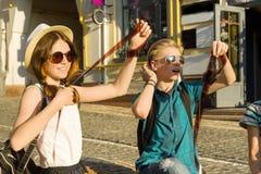 Jugendliche mit Filmfotonegativen des Interesses und der ?berraschung aufpassenden, Stadtstra?enhintergrund lizenzfreie stockbilder