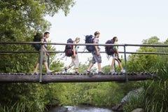 Jugendliche mit Rucksäcken gehend auf Brücke stockbild