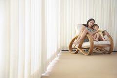Jugendliche mit Schwester Relaxing On Armchair Lizenzfreie Stockfotos