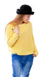 Jugendliche oder junge Frau in der gelben Strickjacke und im schwarzen Hut schauen Lizenzfreies Stockfoto