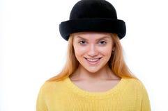 Jugendliche oder junge Frau in der gelben Strickjacke und im schwarzen Hut schauen Lizenzfreie Stockbilder