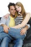Jugendliche Paare, die auf dem Sofa snuggling sind Lizenzfreies Stockfoto
