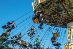 Jugendliche reiten die Stühle an einem reisenden Funfair Lizenzfreie Stockbilder