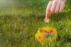 Jugendliche setzt Münze in Sparschwein zu, während der Zukunft zu speichern stockbild
