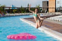 Jugendliche springen in Swimmingpool lizenzfreies stockfoto