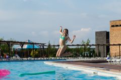 Jugendliche springen in Swimmingpool lizenzfreie stockfotografie