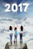 Jugendliche stehen auf Felsen mit 2017 am Himmel Stockbilder
