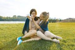 Jugendliche tröstet sie schreiend, gestörten, traurigen Freund Die Mädchen sitzen auf dem grünen Gras im Park lizenzfreies stockbild