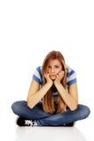 Jugendliche traurige Frau, die auf dem Boden sitzt Lizenzfreie Stockfotos