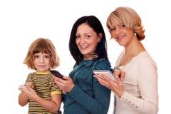 Jugendliche und Frau des kleinen Mädchens mit Telefonen Stockbild