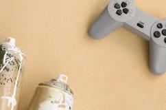 Jugendliche und Jugendlebensstilkonzept Steuerknüppel und zwei Spraydosen liegt auf der Decke des pelzartigen orange Vliesgewebes stockfoto