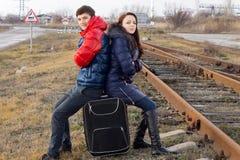 Jugendliche, welche die Aufwartung an der Seite einer Bahn sitzen Stockbild
