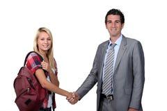 Jugendliche, welche die Hand des Lehrers rüttelt Lizenzfreie Stockbilder