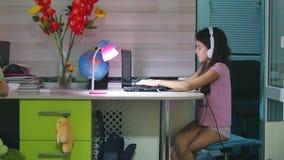 Jugendliche zuhause mit den Kopfhörern, die mit einem Laptop sitzen Schulmädchenmädchen, das Online-Spiel auf Laptopinternet spie stock video