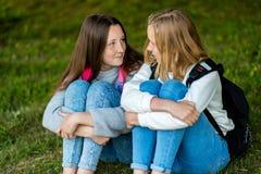 Jugendliche zwei Sommer in der Natur Sie sitzen auf Gras Verständigen Sie sich mit einander Er spricht Intimate lizenzfreies stockbild
