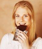 Jugendlicheessenschokoladenlächeln der jungen Schönheit blondes Lizenzfreie Stockfotos