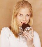 Jugendlicheessenschokoladenlächeln der jungen Schönheit blondes Lizenzfreies Stockfoto
