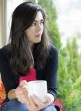 Jugendlicheholding-Kaffeetasse durch Fenster, Stockfoto