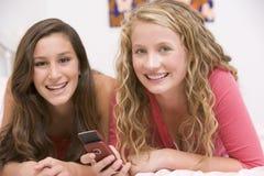 Jugendlichen, die auf Bett unter Verwendung des Handys liegen Stockfotografie