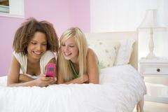 Jugendlichen, die auf Bett unter Verwendung des Mobiltelefons liegen Lizenzfreie Stockfotos