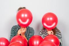 Jugendlichen, die ihre Gesichter hinter Ballonen verstecken Lizenzfreie Stockbilder
