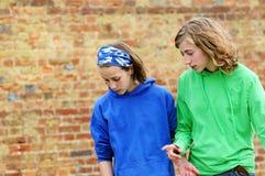 Jugendlichen gegen Backsteinmauer stockfotos