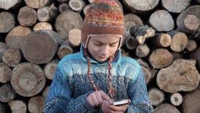 Jugendlicher auf dem Bauernhof, der auf dem Smartphone im Video des Spiels 4K spielt stock video footage