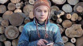 Jugendlicher auf dem Bauernhof, der auf dem Smartphone im Video des Spiels 4K spielt stock footage