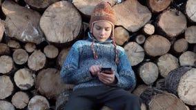 Jugendlicher auf dem Bauernhof, der auf dem Smartphone im Video des Spiels 4K spielt stock video