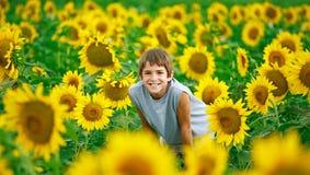 Jugendlicher auf einem Sonnenblume-Gebiet Lizenzfreies Stockbild