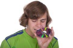 Jugendlicher beißt eine optische Platte Stockfoto