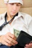 Jugendlicher überprüft die Geldbörse Stockfoto