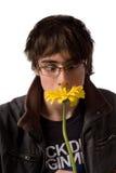 Jugendlicher in den Gläsern, die gelbe Blume riechen Lizenzfreie Stockfotos