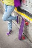 Jugendlicher in den Jeans steht mit Skateboard Stockbild