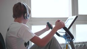 Jugendlicher in den Kopfhörern hörend Musik auf Prüfsystemen eines stationären Fahrrades Turnhalle und gesunder Lebensstil stock footage