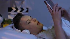 Jugendlicher in den Kopfhörern hörend Musik im Bett, dem Schlag der Vereinbahn glaubend stock footage