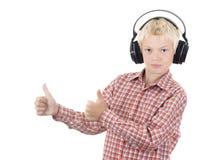 Jugendlicher in den Kopfhörern hört Musik lizenzfreie stockbilder