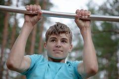Jugendlicher, der Übung auf einer horizontalen Stange tut Lizenzfreie Stockfotografie