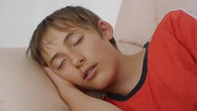 Jugendlicher, der auf Couch schläft Nahaufnahme des kaukasischen jugendlich Jungen im roten T-Shirt schlafend auf beige ledernem  stock video footage