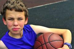 Jugendlicher, der auf dem Basketballplatz sitzt Lizenzfreie Stockfotografie