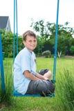 Jugendlicher, der auf einem Schwingen sitzt Stockfotos