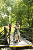 Jugendlicher, der auf einer Fahrradreise auf Holzbrücke sich entspannt Stockfotos
