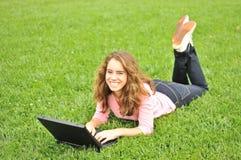 Jugendlicher, der auf Gras mit einem Laptop legt Stockbild