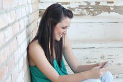 Jugendlicher, der auf Handy texting ist Stockfotografie