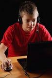 Jugendlicher, der auf Laptop spielt Stockbild