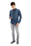 Jugendlicher, der auf seinem Smartphone simst Stockbilder