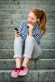 Jugendlicher, der das chcolate schaut im Telefon isst Lizenzfreie Stockbilder